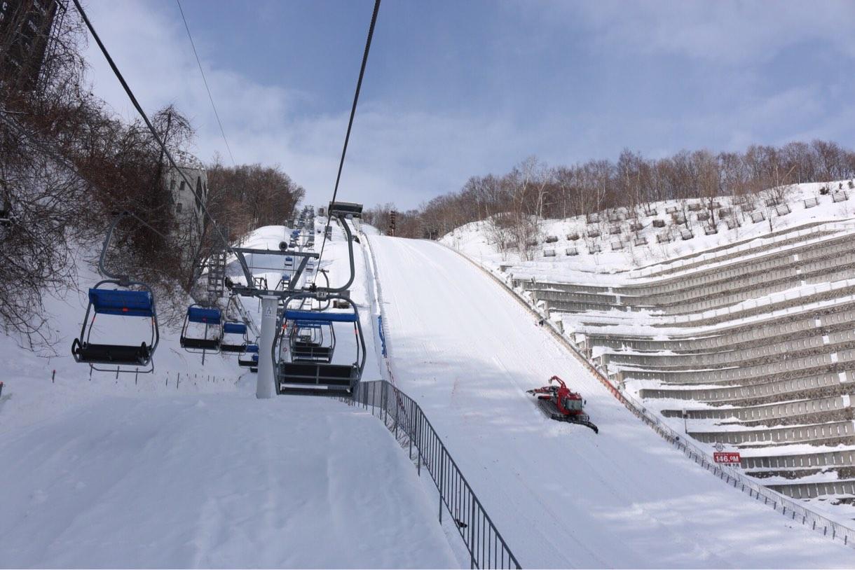 ジャンプ台の急斜面の横をリフトで上昇
